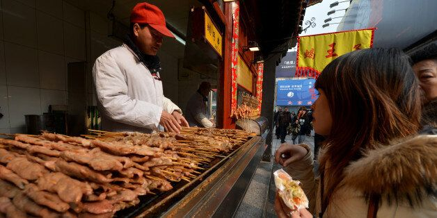 A Chinese hawker barbecues lamb kebabs at his stall in the Wangfujing shopping street of Beijing on February 21, 2013. China is considering a ban on barbecues to help reduce air pollution in built-up areas after heavy smog recently choked large swathes of the country, state media reported. The country's environmental watchdog has issued draft guidelines advising major cities to adopt legislation banning 'barbecue-related activities', risking the ire of street food-loving locals. AFP PHOTO/Mark RALSTON (Photo credit should read MARK RALSTON/AFP/Getty Images)