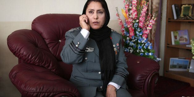 Afghanistan's first-ever female district police chief, Col. Jamila Bayaz, 50, talks to the phone at her office in Kabul, Afgh