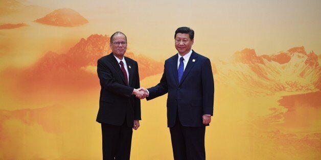 Philippine President Benigno Aquino (L) shakes hands with China's President Xi Jinping as he arrives for the Asia-Pacific Eco