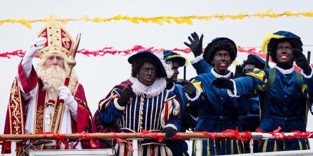 Actors dressed as Saint Nicolas, left, and Black Pete arrive on a boat in Antwerp, Belgium on Saturday, Nov. 15, 2014. Across