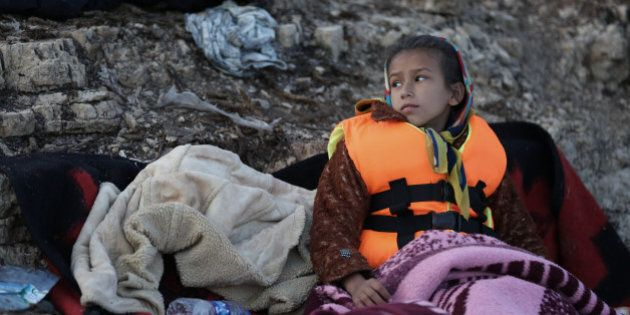 A child looks around as migrants prepare to travel by dinghy to the Greek island of Chios, from Turkish...