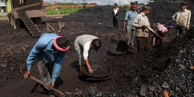 In this July 1, 2013 photo, Indian laborers dig a roadside coal depot at Khliehriet in Meghalaya, India. For six years in a r