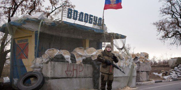 A pro-Russian gunman stands guard at a checkpoint with a Russian flag near Kharzisk, East of Donetsk, on November 16, 2014. W