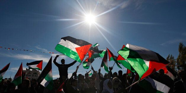 Palestinians wave flags as they celebrate their successful bid to win U.N. statehood recognition in the West Bank city of Ram