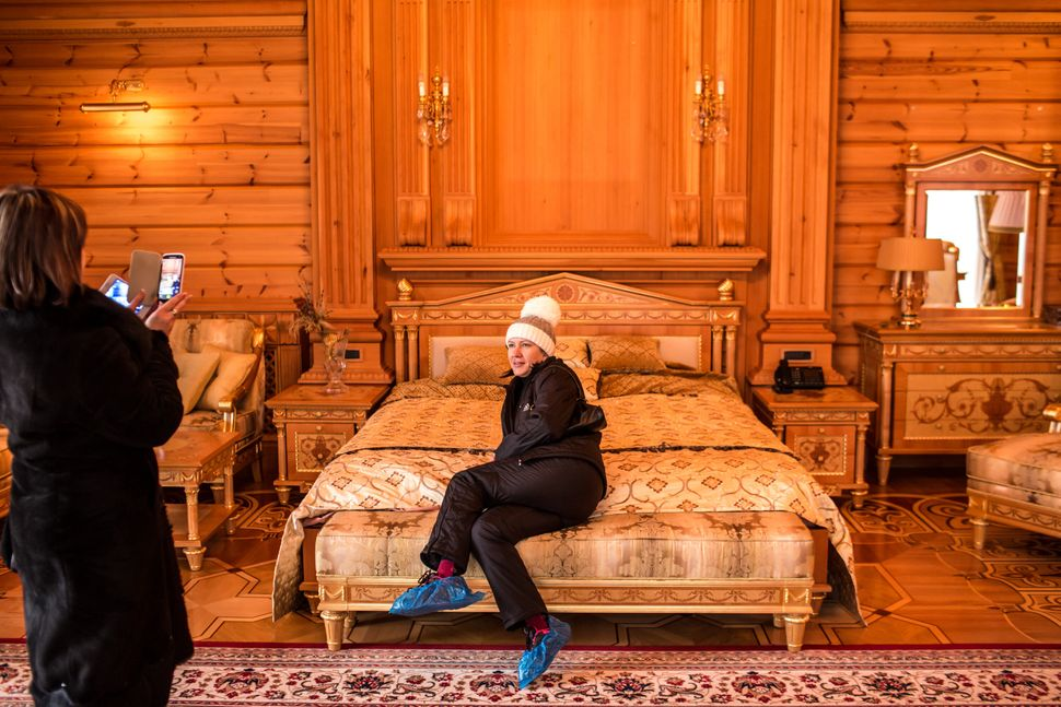 Visitors pose for pictures on the bed of former Ukrainian president Viktor Yanukovych at Mezhyhirya, his former private estat