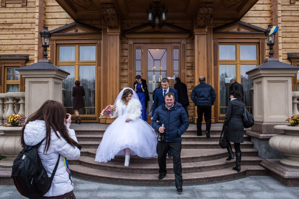 A bride and groom pose for pictures at Mezhyhirya, the former private estate of former president Viktor Yanukovych which is n