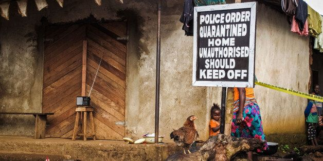 A child, center, stands underneath a signboard reading 'Police order quarantined home unauthorised should keep off' as a fami