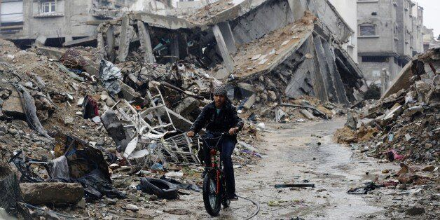 A Palestinian rides his bike past houses that were destroyed during the 50-day Gaza war between Israel and Hamas-led militant
