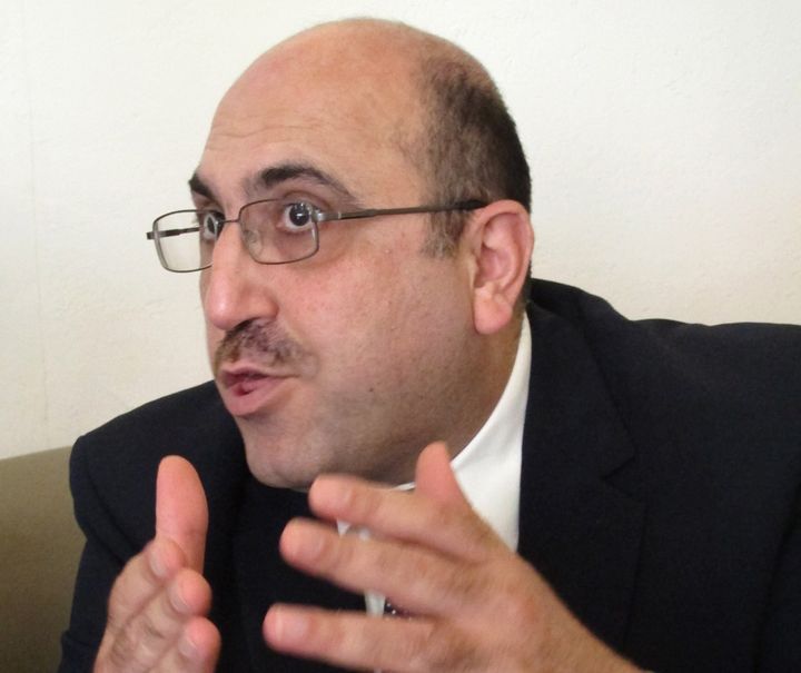 In this photo taken on Wednesday, Oct. 10, 2013,  Rami Abdurrahman, gestures during an interview with The Associated Press in