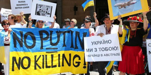 Anti-Russian protesters hold banners at a rally during the G-20 in Brisbane, Australia, Saturday, Nov. 15, 2014. The proteste