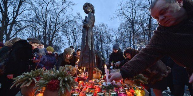 People place candles in memory of the victims of the Holodomor famine during a ceremony at the Holodomor memorial in Kiev on November 22, 2014. Ukraine marked 81 years since the Stalin-era Holodomor famine, one of the darkest pages in its entire history that left millions dead and which is regarded by many as a genocide. The 1932-33 famine took place as harvests dwindled and Soviet leader Josef Stalin's police enforced the brutal policy of collectivising agriculture by requisitioning grain and other foodstuffs. AFP PHOTO/ SERGEI SUPINSKY (Photo credit should read SERGEI SUPINSKY/AFP/Getty Images)