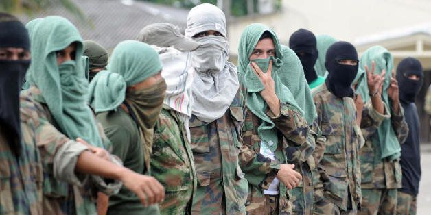 Members of 'Los Rastrojos' bandit group cover their face with towels and balaclavas as they surrender at the Voltigeros Batta