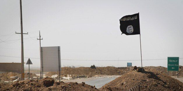 A flag of the Islamic State (IS) is seen on the other side of a bridge at the frontline of fighting between Kurdish Peshmerga