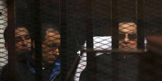 Ousted Egyptian President Hosni Mubarak, 86, lies on a gurney, next to his son Gamal, second left, in the defendants cage, du