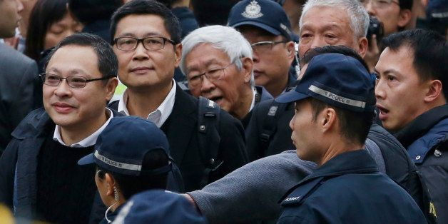 Four protest leaders, from left, Benny Tai Yiu-ting, Chan Kin-man, Joseph Zen and Chu Yiu-ming, surrounded by police officers
