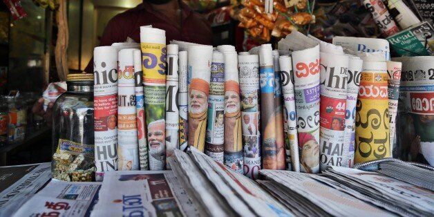 Indian newspapers with front pages featuring opposition leader Narendra Modi are on display at a stall in Bangalore, India, S