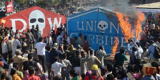 Indian residents and Bhopal Gas disaster survivors set alight a banner of Union Carbide as they commemorate the 30th annivers