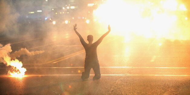 FERGUSON, MO - AUGUST 17:  Tear gas reigns down on a woman kneeling in the street with her hands in the air after a demonstra