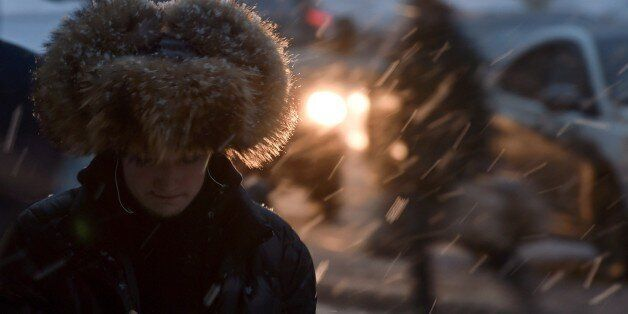A man walks along a street in central Moscow during a snowfall on December 10, 2014. AFP PHOTO / KIRILL KUDRYAVTSEV        (P