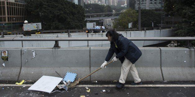 A worker cleans the street after Hong Kong police dismantled the main pro-democracy protest camp in the Admiralty district of