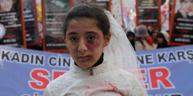 A Turkish girl, wearing a wedding dress and covered with fake bruises, stands in front of other protesters holding placard re