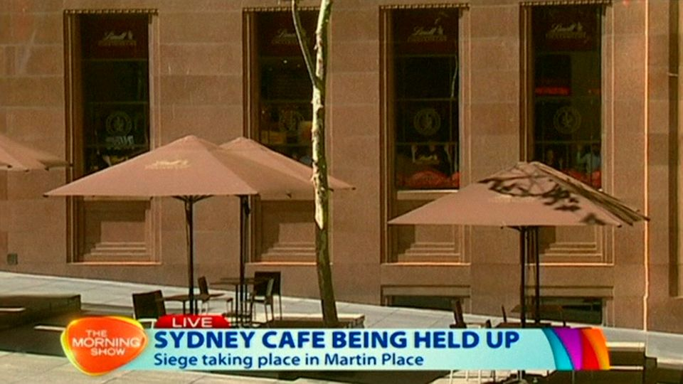This image taken from video shows people against shop windows holding up hands inside a cafe in Sydney, Australia Monday, Dec