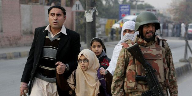 Pakistani parents escort their children outside a school attacked by THE Taliban in Peshawar, Pakistan, Tuesday, Dec. 16, 201
