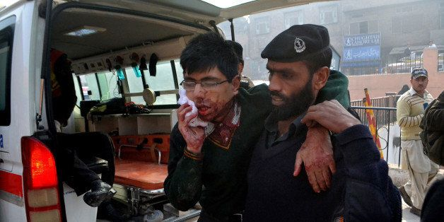 A hospital security guard helps a student injured in the shootout at a school under attack by Taliban gunmen in Peshawar, Pak