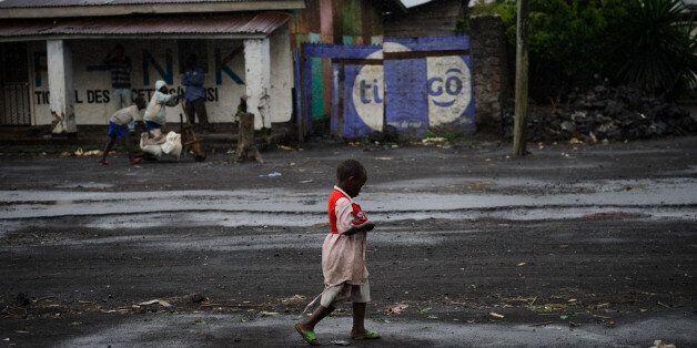 A young Congolese walks through the rain in the town of Sake, west of Goma, in the east of the Democratic Republic of Congo on November 28, 2012. The government accused rebels today of widespread looting in Goma as the fighters began pulling out of the strategic eastern city following diplomatic mediation to prevent the conflict spreading across the volatile region. AFP PHOTO/PHIL MOORE (Photo credit should read PHIL MOORE/AFP/Getty Images)