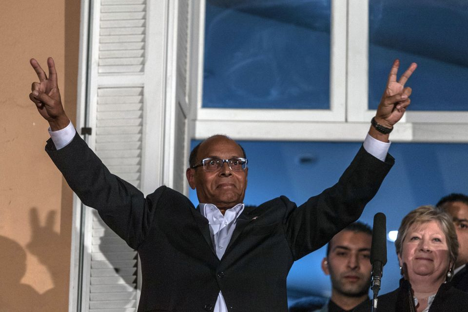 Tunisian presidential candidate Moncef Marzouki makes the V sign prior to give a speech, after the second round of the countr