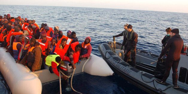 In this photo released by the Italian Navy Thursday, March 20, 2014, migrants stand on a dinghy after being rescued along the