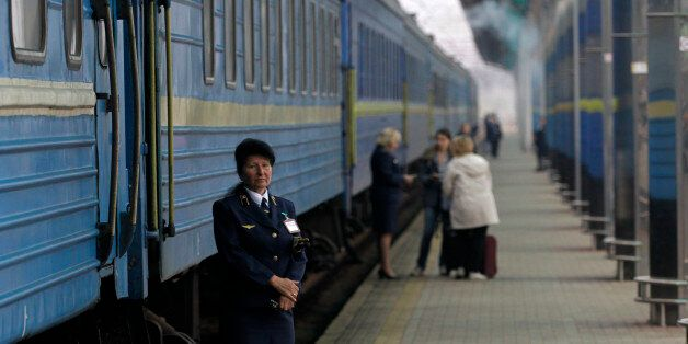 A Ukrainian railways employee stands in front of a first train departing from the Donetsk to Sevastopol, Crimea at Donetsk's