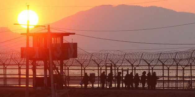 South Korean soldiers patrol along iron fence in Paju near the Demilitarized Zone (DMZ) dividing the two Koreas on December 1