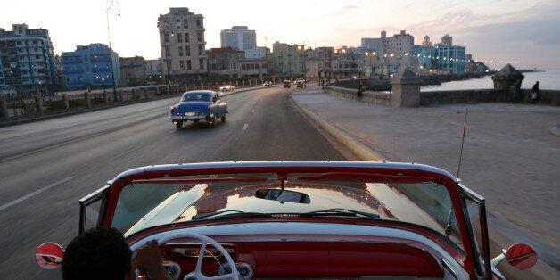 In this Sunday, Dec. 21, 2014 photo, Michel Salgado drives his 1957 Mercury Monterey convertible along the Malecon in Havana,