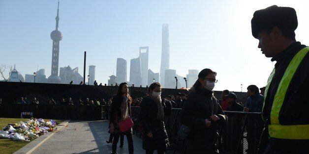 Three mourners walk past a security guard (R) after placing flowers at the site of the New Year's Eve stampede at the Bund in