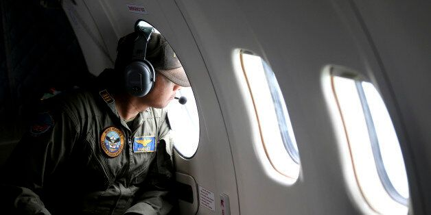 A crew member of Indonesian Navy's CN-235 transport plane looks out of a window during a search operation for victims of the