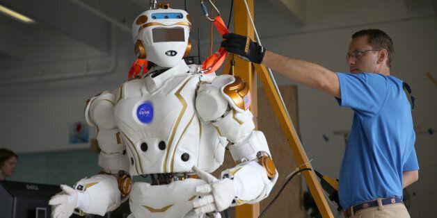 HOMESTEAD, FL - DECEMBER 21:  Court Edmondson works on the team NASA robot during the DARPA Robotics Challenge Trials at the