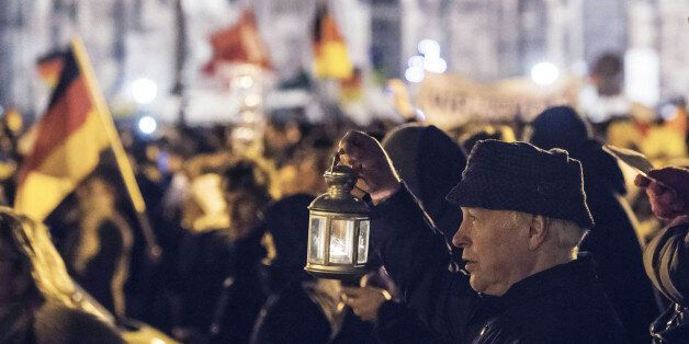 A participant of a rally called 'Patriotic Europeans against the Islamization of the West' (PEGIDA) holds a hand lantern and