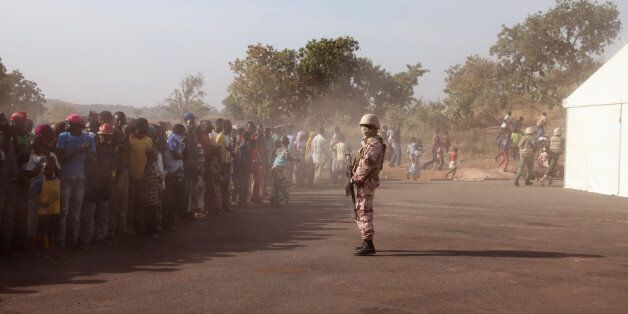In this photo taken Monday, Nov. 17, 2014, a Mali soldier, center, controls a crowd of people during a visit by their president, Ibrahim Boubacar Keita, at the border village of Kouremale, Mali, between Mali and Guinea. On Mali's dusty border with Ebola-stricken Guinea, travelers have a new stop: Inside a white tent, masked medical workers zap incomers with infrared thermometer guns and instruct them to wash their hands in chlorinated water. (AP Photo/Baba Ahmed)