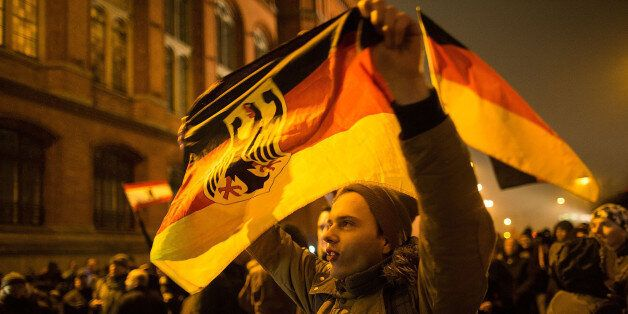 BERLIN, GERMANY - JANUARY 05:  A supporter of the Pegida movement holds a flag while supporters gather for a march in their f