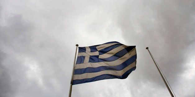 A Greek national flag flies from a pole beneath stormy skies outside the Hellenic Stock Exchange in Athens, Greece, on Wednes