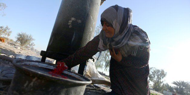 An Iraqi woman displaced by fighting, between government supporters and the Islamic State (IS) group, uses hot water to wash