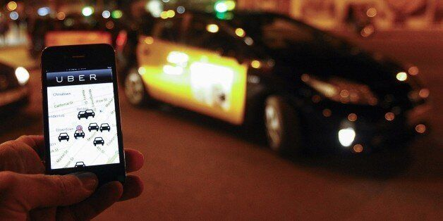 The Uber app is seen on a smartphone past cabs waiting for clients near the Sagrada Familia in Barcelona, on December 9, 2014