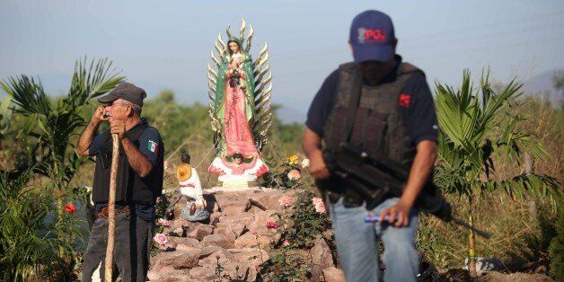 A policeman stands guard at the crime scene after 11 people were killed in La Ruana, Michoacan state, Mexico on December 17,