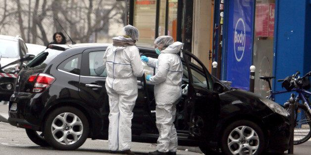 Forensic experts examine the car believed to have been used as the escape vehicle by gunmen who attacked the French satirical