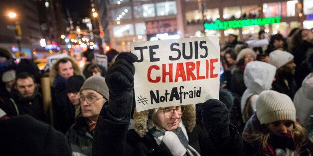 "A mourner holds a sign that reads ""I AM CHARLIE"" in French during a rally in support of Charlie Hebdo, a French satirical wee"