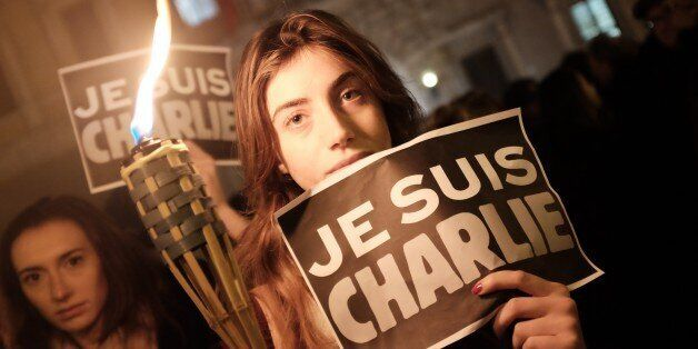 A woman holds a torch and a poster reading 'I am Charlie' in front of the French embassy on January 8, 2015 in Rome during a