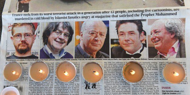 Candles are placed on a newspaper bearing pictures from (L) of French satirical weekly Charlie Hebdo's editor and cartoonists