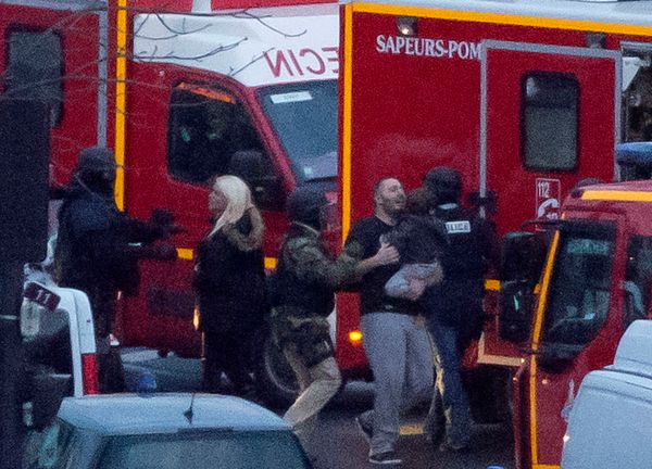 A security officer directs released hostages after they stormed a kosher market to end a hostage situation, Paris, Friday, J