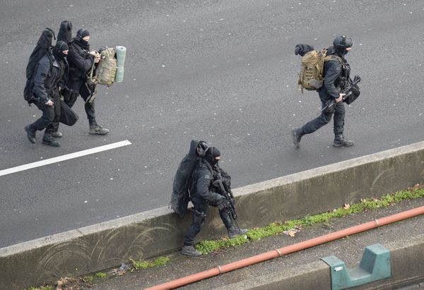 Members of the French police special force RAID walk with their equipment on the 'peripherique' (circular road) in Porte de V
